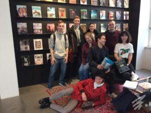 Eine Gruppe von jungen Menschen sitzt oder steht vor einer Regalwand, auf der Zeitschriften mit bunten Titelseiten ausgestellt sind.