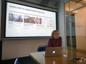Laura Himmelreich sitzt vor einem Notebook an einem Konferenztisch. Hinter ihr ist auf einer Leinwand eine Reihe von Artikel-Teasern zu sehen, wie sie auf der Homepage von VICE dargestellt sind.